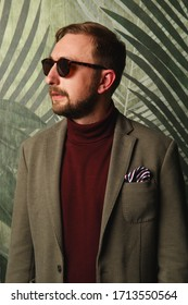 Portrait of young beautiful fashionable man, in sunglasses, olive jacket against wallpaper with greenery. Hipster style guy looking aside