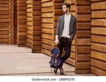 Portrait of young beautiful fashionable man against wooden wall. Hipster style guy