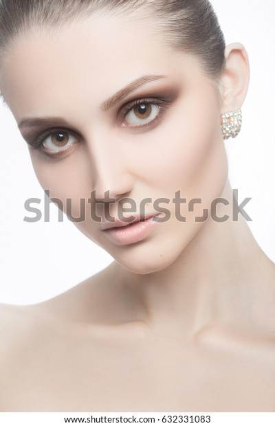 Portrait of young beautiful female with evening makeup and earrings looking at camera on white background.