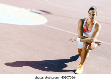 Portrait of a young beautiful fit woman outdoors stretching