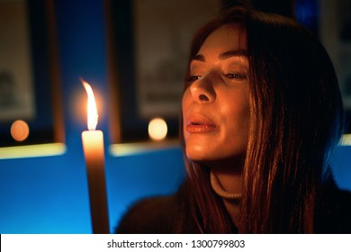 Portrait of a young beautiful fortune teller woman in a mysterious vintage setting with coffee and candles