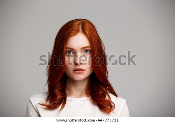 Portrait of young beautiful ginger girl over gray background.