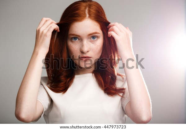 Portrait of young beautiful ginger girl over gray background with back light.