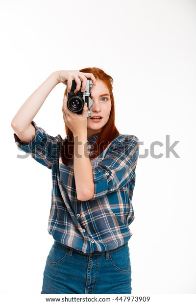 Portrait of young beautiful ginger photographer over white background.