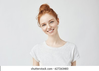 Portrait of young beautiful ginger woman with freckles cheerfuly smiling looking at camera. Isolated on white background. Copy space.