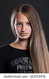 Portrait of young beautiful girl with blond long hair and blue eyes no makeup, studio shot, dark background