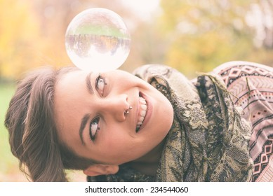 Portrait of young beautiful girl with blue eyes balancing a crystal ball on the head - Woman performing contact juggling in a park