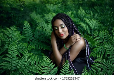 Portrait of a young beautiful girl with box braids hairstyle on the green nature background