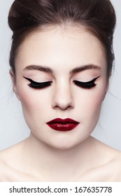 Portrait of young beautiful girl with cat eyes and red lips