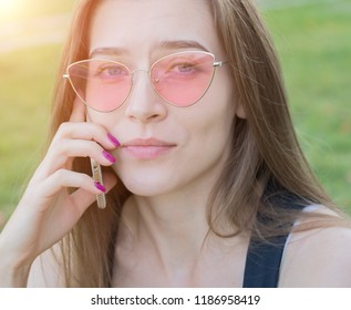 portrait of a young beautiful girl close up with cell phone in park