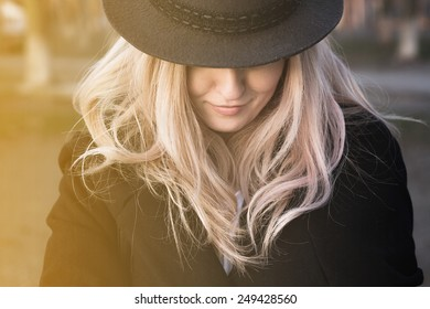 Portrait of young beautiful girl closing hat half of the face