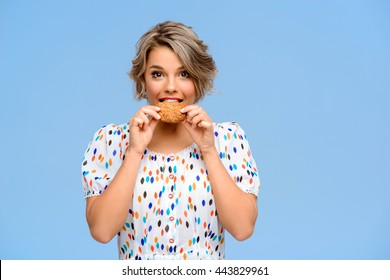 Portrait of young beautiful girl eating cookie, smiling, looking at camera over blue background. Copy space.