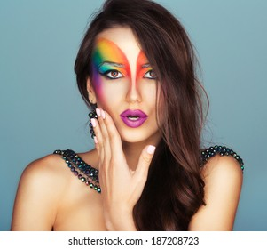 Portrait of a young beautiful girl with a fashion bright multicolored makeup of eyes