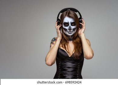 Portrait of young beautiful girl with fearful halloween skeleton makeup  Katrina Calavera in headphones listening to music on gray background.