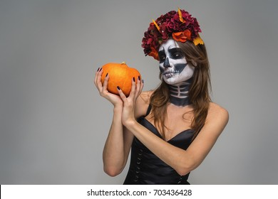 Portrait of young beautiful girl with fearful halloween skeleton makeup with a wreath Katrina Calavera made of flowers on her head, holding pumpkin over gray background