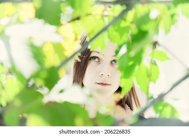 Portrait of a young beautiful girl in the foliage closeup