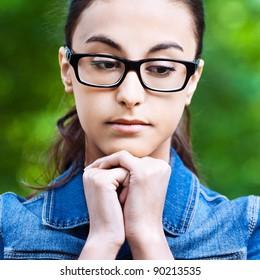 portrait young beautiful girl glasses park upset sad