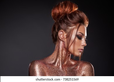 Portrait of a young beautiful girl with gold and bronze sparkles. Hairstyle of red hair, clean, tanned skin, beautiful bright makeup, pink lipstick on lips. Beauty of the face model.