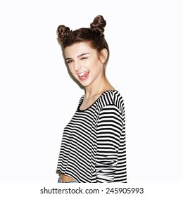 Portrait of young beautiful girl having fun and showing tongue. Bright makeup and top knot hairdo. White background, not isolated. Inside.