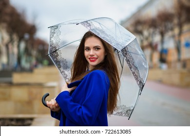 Portrait of young beautiful girl hiding under an umbrella from a small rain. View of the model is directed to camera