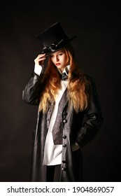 Portrait of a young beautiful Girl with long red hair in black with a top hat,sexy Woman in a black leather coat.Beautiful face.Closeup portrait of a caucasian Attractive young Woman.Beauty portrait