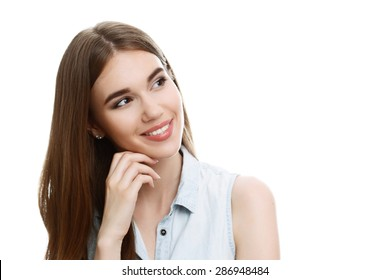 Portrait of a young beautiful girl with long brown hair wearing blue denim blouse, smiling and holding her hand near face looking to the left tilting her head, isolated on white background