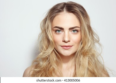 Portrait of young beautiful girl with long messy hair and clean make-up