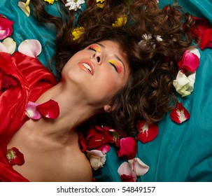 portrait of a young beautiful girl with long curly hair, decorated with many flowers, lying on a turquoise background