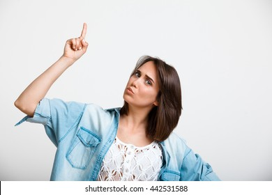 Portrait of young beautiful girl looking at camera, pointing fingers up over white background. Copy space.