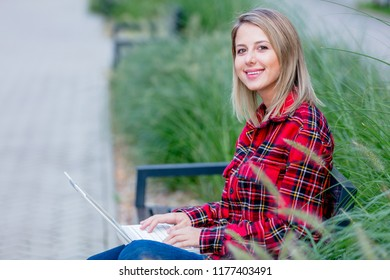 Portrait of a young beautiful girl with notebook computer sitting at bench near a house.