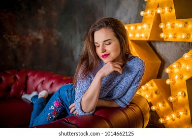 Portrait of a young beautiful girl on a red sofa