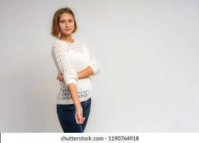 Portrait of a young beautiful girl on a white background. She is in front of the camera in different poses with different emotions.