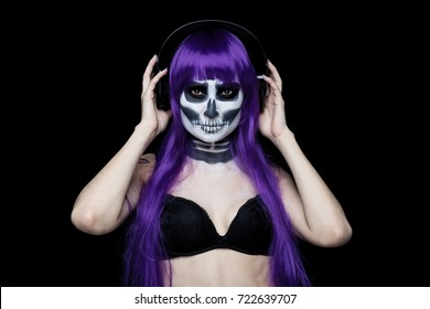 Portrait of young beautiful girl of purple hair (wig)  with fearful halloween skeleton makeup  Katrina Calavera in headphones listening to music on black background