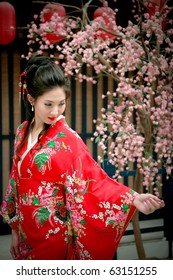Portrait of young beautiful girl in red kimino dress touching sakura flower