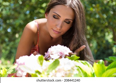 Portrait of young beautiful girl smells flowers, against green summer garden.