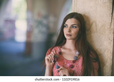 Portrait of a young beautiful girl standing near a column close-up