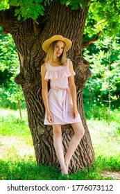 Portrait of a young beautiful girl in a summer dress posing in the shade of an oak
