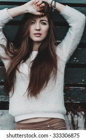 Portrait of young beautiful girl in trendy clothes posing alone over wood wall. Perfect skin and make-up.