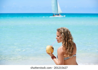 Portrait of young beautiful girl at tropical beach for vacations in Varadero, Cuba, drinking cocktail in coconut and sitting on sand