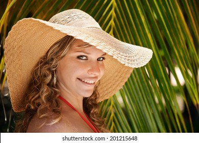 Portrait of young beautiful girl at tropical beach for vacations, looking at camera and smiling