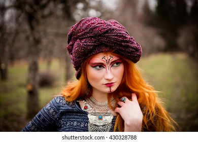 Portrait of a young beautiful girl in a turban in the autumn garden