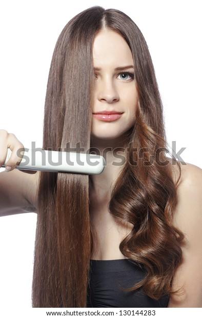 Retrato de una joven hermosa chica usando estilista en su brillante cabello
