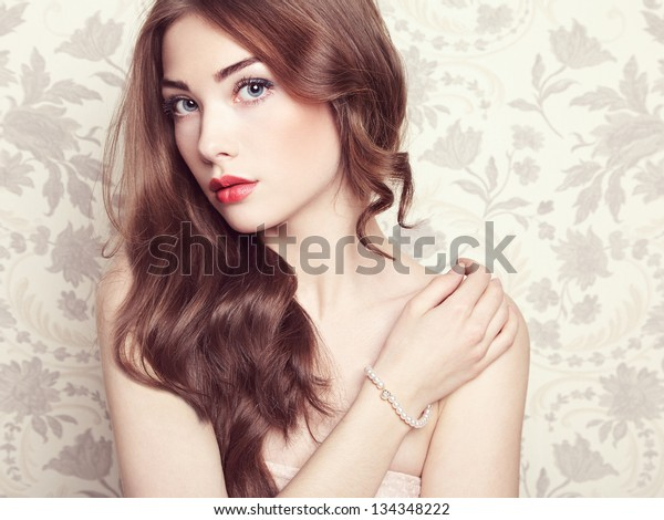 Portrait of young beautiful girl with wavy hair. Fashion photo