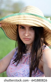 Portrait of a young beautiful girl wearing a straw hat in nature