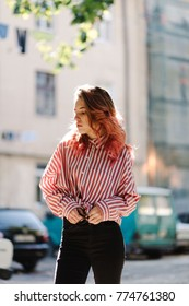 Portrait of young beautiful girl wearing stylish shirt, black skinny jeans, glasses. Girl have shiny long red hair. Female fashion concept