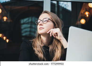 Portrait of a young beautiful girl wearing eyeglasses sitting in front of laptop at cafe. Concept of business woman.