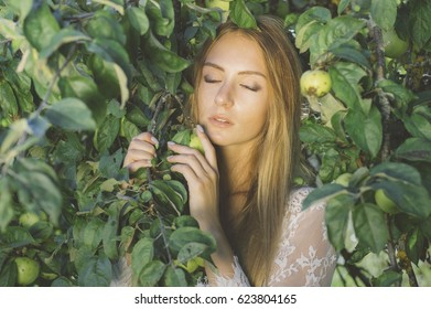 Portrait of young beautiful girl in white lace dress in apple garden, in the tree crown, closed eyes
