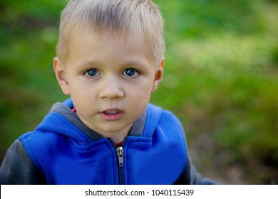 Portrait of a young beautiful guy with a serious face. A child with a happy and cheerful face, with blue eyes and a confident look.