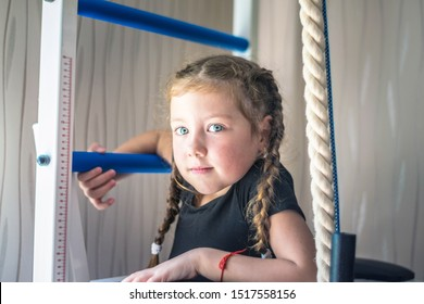 Portrait of young and beautiful gymnast in gymnastic leotard. Little girll goes in for sports on climbing frame. Sports child climbs the stairs. Children's sports concept