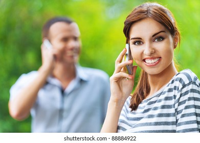 portrait young beautiful happy couple man woman talking phone background summer green park